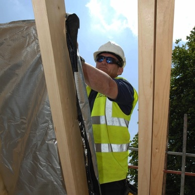 workman insulating a timber frame